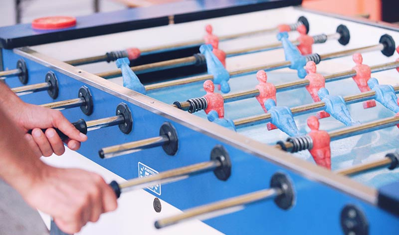 Playing table football in games room